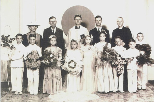 "Father Emil Kapaun (center) poses for a picture with members of his congregation after celebrating his first Mass as a priest at St. John Nepomucene Church in Pilsen, Kan., in 1940. Kapaun would go on to serve as a U.S. Army chaplain, both in World War II and the Korean War, where his selflessness and dedication would endear him to his fellow Soldiers as a ""Soldier's chaplain."""
