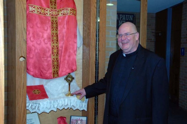 Rev. John Hotze, judicial vicar for the Wichita Dicocese, describes Father Emil Kapaun's vestments, on display at Kapaun Mt. Caramel Catholic High School in Wichita, Kan. The school, named after Kapaun, has many of his personal effects on display. Kapaun served as an Army chaplain during World War II and the Korean War. His heroic actions during the latter earned him the Distinguished Service Cross, which will be upgraded to the Medal of Honor in an April 11, 2013, White House ceremony.