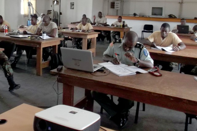 Eighteen officers and NCOs from the Armed Forces of Liberia complete workbook information during a familiarization class on Inspector General operations event conducted by U.S. Army Africa's Capt. James Watson and Sgt. 1st Class Bobby Conn recently.