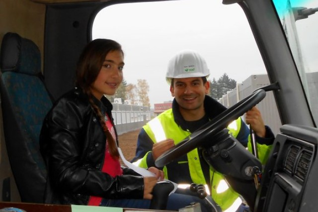 Asad Mirza, a Wayss & Freytag Engineering AG project engineer and safety briefing organizer, helps a student from NATO's Supreme Headquarters Allied Powers Europe International School play the role of truck driver Nov. 9 as part of a vehicle blind spot safety demonstration in Mons, Belgium.