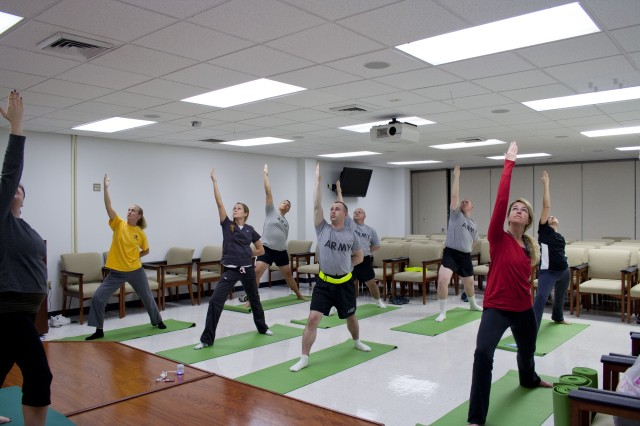 Soldiers and retirees practice reverse warrior pose during a lunch-time yoga class.