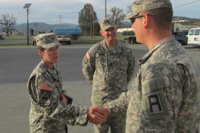 Col. Carolyn Birchfield, left, commander of Division West's 402nd Field Artillery Brigade from Fort Bliss, Texas, coins Sgt. Matthew Rado, a member of the 3-356th Logistics Support Battalion, 402nd Field Artillery Brigade, from Fort Hunter Liggett, Calif., as Command Sgt. Maj. David Adams, the battalion's senior enlisted advisor, looks on last month at Fort Hunter Ligget. Rado was one of several 3-356th Soldiers recognized for their accomplishments during the Army Reserve's annual Warrior Exercise and Combat Service Training Exercise held at the installation in March and April. (Photo by Maj. Stephen Messenger, 3-356th Logistics Support Battalion, 402nd Field Artillery Brigade, Division West)
