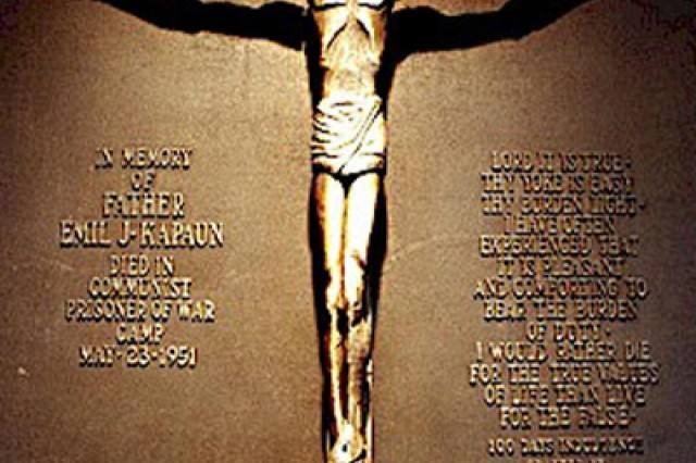 This crucifix was carved by Maj. Gerald Fink, United States Marine Corps, in Prison Camp No. 5. Although he arrived at the North Korean prisoner of war camp after U.S. Army Chaplain Emil Kapaun died, Fink was so impressed with the stories fellow prisoners would tell about Kapaun, that he carved the figure in the chaplain's likeness. The crucific was smuggled out of the camp at the end of the war, and brought to the Wichita Diocese in Kansas. It now hangs in Kapaun Mount Carmel Catholic High School in Wichita, Kan.