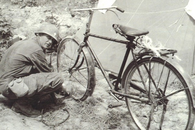 Chaplain (Capt.) Emil Kapaun fixes a flat on his bicycle in Korea, August 1950. Kapaun often rode this bike from location to location along the fighting lines to visit Soldiers.