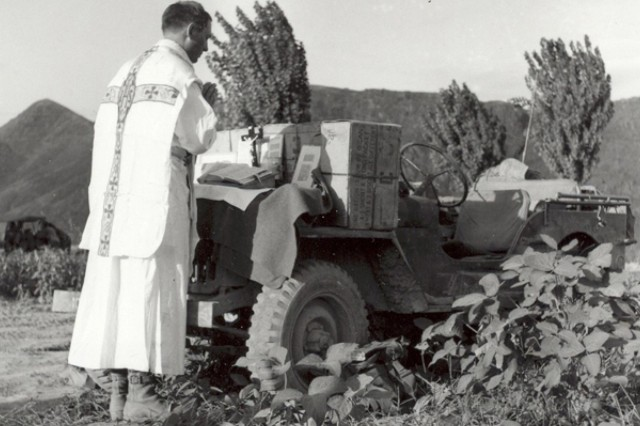 Chaplain (Capt.) Emil Kapaun conducts a field Mass on the hood of his jeep in Korea, Aug. 11, 1950. It was common practice for Kapaun to travel to the front lines to conduct religious services and offer care and comfort to Soldiers.
