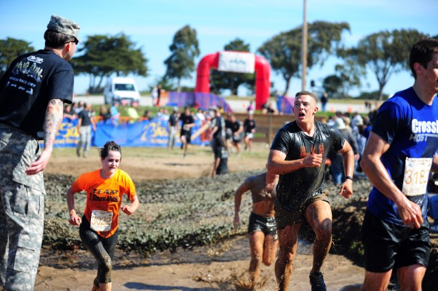 """PRESIDIO OF MONTEREY, Calif. -- A volunteer """"drill sergeant"""" provides motivation as runners exit the course's final mud pit."""