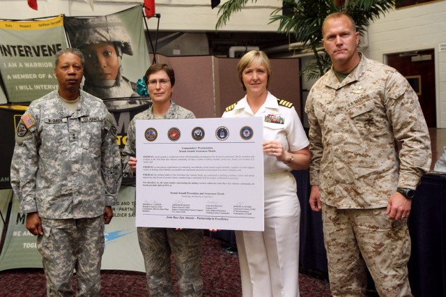 "FORT SAM HOUSTON, Texas "" Military commanders for several Fort Sam Houston units pose with the newly-signed Commander's Proclamation on Sexual Assault Awareness April 3 during the installation's Sexual Assault Awareness Month observance at the Warrior and Family Services building.  (From left to right) Maj. Gen. Adolph McQueen, Jr., deputy commanding general for support, U.S. Army North (Fifth Army), Brig. Gen. Theresa Carter, commander, 502nd Air Base Wing and Joint Base San Antonio, Capt. Gail Hathaway, commander, Navy Medicine, Education and Training Command and Lt. Col. Robert Sotire, commander, 4th Marine Reconnaissance Battalion, I-I Staff. This year's theme is ""We own it … We'll solve it … Together."""