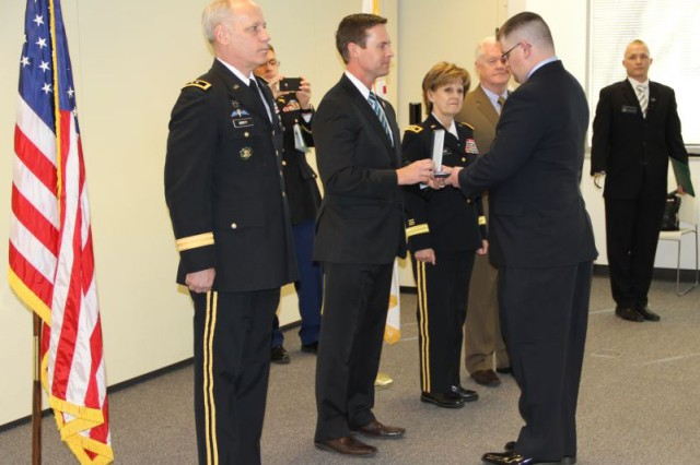 U.S. Rep. Rodney Davis presents the Soldiers Medal to Staff Sgt. (Ret.) Mark Rodgers, a former 80th Training Command (TASS) Soldier during a ceremony in Champaign, Ill., April 4, 2013. Rogers received the medal for rescuing his family from a burning car after an accident in Arkansas, July 22, 2008. Standing to Davis' left is Maj. Gen. Bill Gerety, commander 80th Training Command (TASS). To left, Maj. Gen. Karen LeDoux, commander 88th Regional Support Command, and Army Reserve Ambassador John Moulton