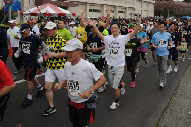 Adult runners take off from the start of a run held during April 6 during Camp Zama's Cherry Blossom Festival.