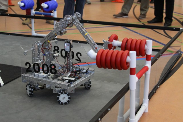 A robot retrieves a ring from the dispenser to score points.