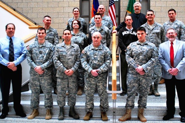 Instructors Thomas Ferguson (far right, front), Army Sustainment Command, Rock Island Arsenal, Ill., and Robert Farr (far left, front), a certified Master Black Belt for Lean Six Sigma, 404th Army Field Support Brigade, gather with recent Lean Six Sigma Green Belt training students at their graduation ceremony held March 28 at the Army Reserve Readiness Center at Joint-Base Lewis-McChord. (Photo by Greg Alderete, 404th AFSB Public Affairs)