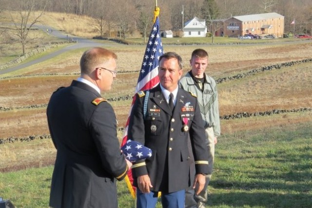 Col.  Jim Brundage presents Lt. Col. Brian De Toy a folded American flag during his retirement ceremony at Gettysburg National Military Park, Pa., April 6, 2013. Cadets from West Point's defense and strategic studies program attended the ceremony during their staff ride to battlefield. (U.S. Army photo/released)