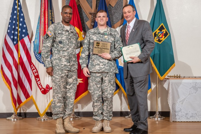 Spc. Andrew Lee, 515th Engineer Sapper Company, 5th Engineer Battalion, 4th Maneuver Enhancement Brigade, center, receives the 2013 Fort Leonard Soldier of the Year award and Army Commendation Medal from Command Sgt. Maj. Terrence Murphy, Maneuver Support Center of Excellence and Fort Leonard Wood command sergeant major, left, and retired Command Sgt. Maj. Merle Jones, right, April 5, 2013 in Lincoln Hall Auditorium.