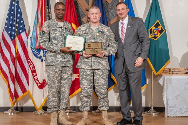 Staff Sgt. Jonathan James, D-Company, 787th Military Police Battalion, 14th MP Brigade, center, receives the 2013 Fort Leonard Wood Drill Sergeant of the Year award and Army Commendation Medal from Command Sgt. Maj. Terrence Murphy, Maneuver Support Center of Excellence and Fort Leonard Wood command sergeant major, left, and retired Command Sgt. Maj. Merle Jones, right, April 5, 2013 in Lincoln Hall Auditorium.