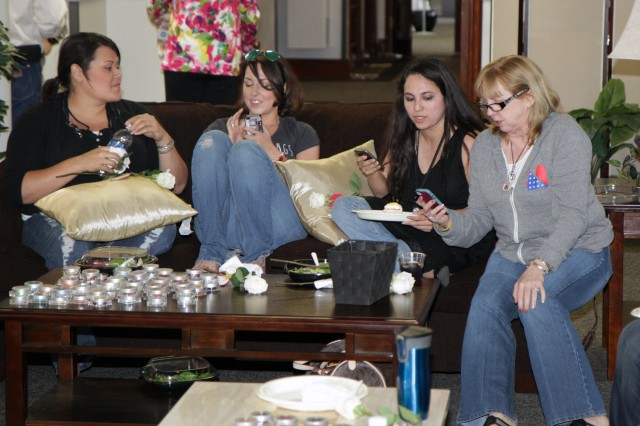 Raquel Scates, Taryn Davis, Ana Perez and Karen Riecke look over their contact lists on their phones and compare notes to determine who was en route to the casual lunch, April 5, 2013, at the Survivor Outreach Services' Hall of Remembrance on Fort Sam Houston, Texas. Friends and Gold Star Wives gathered together during the second annual Gold Star Wives Day.