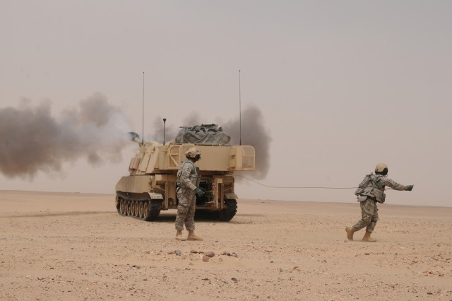 """CAMP BUEHRING, Kuwait. """" Specialist Christopher Pearsall, cannon crewmember, Company B, 4th Battalion, 42nd Field Artillery Regiment, 1st Armored Brigade Combat Team, 4th Infantry Division, uses a 50-foot lanyard to fire the first round from a M109A6 Paladin self-propelled howitzer, during Table VI Certifications at Udairi Range, Kuwait, April 3, 2013. Artillerymen fire the first round of an exercise from a distance as a safety precaution against mechanical damages sustained during travel."""