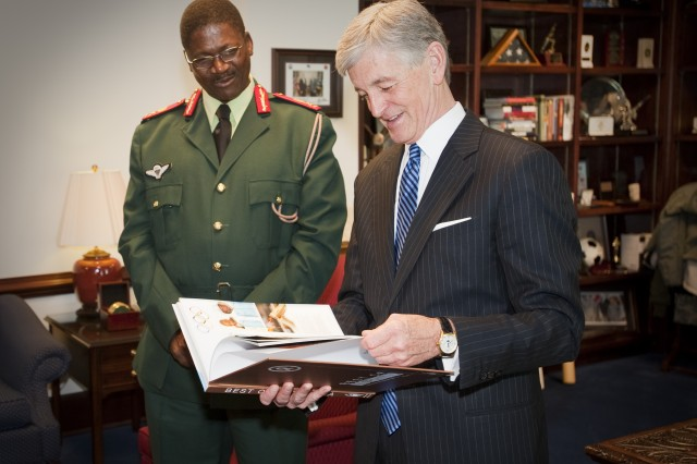 Secretary of the Army John McHugh examines a book presented to him by Botswana Defence Force Commander Lt. Gen. Gaolothe Galebotswe during an official visit to the Pentagon in Washington, D.C., April 9, 2013.  (U.S. Army photo by Spc. John G. Martinez)