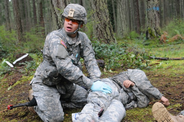 Pfc. Robert Pacheco, a native of Amsterdam, N.Y., assigned to 10th Combat Support Hospital, applies pressure to a simulated wound as part of Expert Field Medical Badge qualification, April 8. Approximately 250 medical soldiers from across the U.S. will attempt to earn the Expert Field Medic Badge April 7-12. Of those who participate, an estimated 20 percent or less usually qualify at the end. (Photo by Staff Sgt. Mark Miranda, 5th Mobile Public Affairs Detachment)