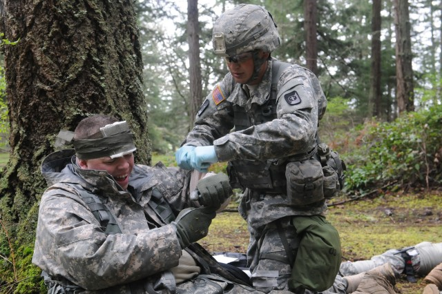 Spc. Mark Becker (right), a native of Faribault, Minn., places a splint on Spc. Jason Hayes' simulated injury as part of Expert Field Medical Badge qualification, April 8. Approximately 250 medical soldiers from across the U.S. will attempt to earn the Expert Field Medic Badge April 7-12. Of those who participate, an estimated 20 percent or less usually qualify at the end. (Photo by Staff Sgt. Mark Miranda, 5th Mobile Public Affairs Detachment)