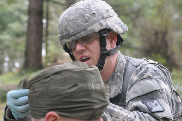 Sgt. Joshua Engstrom, 47th Combat Support Hospital, treats a soldier's simulated head injury as part of Expert Field Medical Badge qualification, April 8. Approximately 250 medical soldiers from across the U.S. will attempt to earn the Expert Field Medic Badge April 7-12. Of those who participate, an estimated 20 percent or less usually qualify at the end. (Photo by Staff Sgt. Mark Miranda, 5th Mobile Public Affairs Detachment)