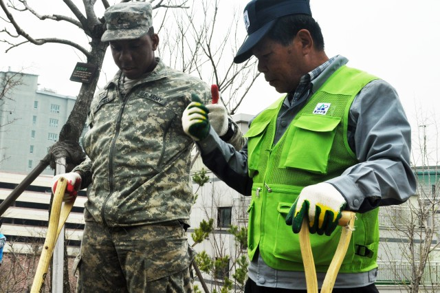 Pfc. Daron L. Mitchell, a solider from 106 Medical Detachment, and a Yongsan-gu employee give thumbs up after successfully planting a tree during the National Arbor Day event at Singye historic park, April 5. (U.S. Army photo by Pfc. Lim Hong-seo)