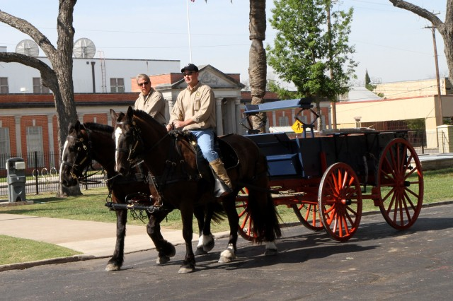 "FORT SAM HOUSTON, Texas "" John Deeley (left), the stable master for the U.S. Army Military Honors Platoon, Caisson Section, and Staff Sgt. Lisle Childers, a section leader with the Caisson Section, guide Wooldridge and Dunaway April 5 as the horses pull a replica of an 1870s Four-Mule Army Escort Wagon near the historic Quadrangle. The wagon will go on display at the Fort Sam Houston Museum when it moves to the Quadrangle early 2014; it can also be used by U.S. Army North (Fifth Army) during parades and other public events. The escort wagon was approved by the Secretary of War in 1878 as the replacement for the Civil War six-mule wagon. This type of wagon, which could carry 3,000 pounds, was a common site at the Quadrangle in the late 19th Century as the post was originally built as a supply depot. The ""leaden blue"" and ""venetian red"" coloring of the wagon is consistent with the original coloring of military wagons, which were painted similar to the Conestoga wagon used during the Revolutionary War. The wagons were used by the Army until 1939."