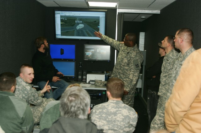 Sgt. 1st Class Keldrick Moore (standing, pointing) of the Virtual Clearance Training Suite fielding team explains the after-action review phase of the simulation program.