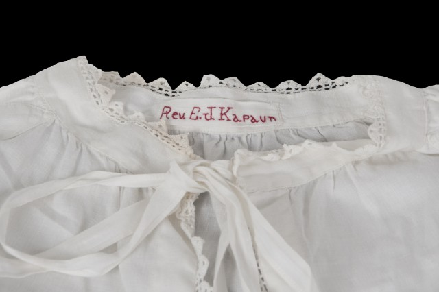The white surplice would have been worn over the black cassock and priestly garb of the day. This surplice features hand-stitched embroidery, perhaps added to the garment by Emil's mother, Elizabeth.
