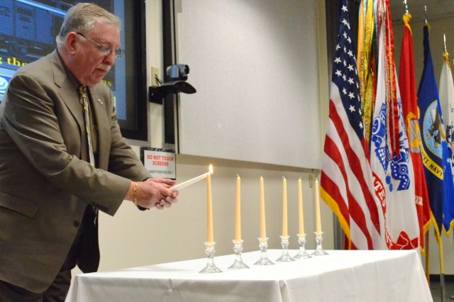 Joseph Koek, guest speaker and Jewish Holocaust survivor, lights the first candle at the National Days of Remembrance observance in the Baylor Conference Room, Building 103 on April 9. (Photo by Jasmine Phillips, ASC Public Affairs)