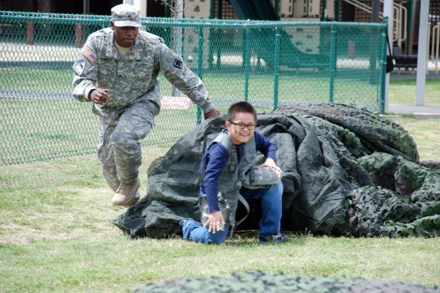 Sgt. Martin Teabout of the 470th Military Intelligence Brigade prompts a student to the next obstacle during field day at Bowden Elementary School April 5. The brigade conducted the field day in partnership with the school as part of the Joint Base San Antonio Adopt-a-School Program. (U.S. Army photo by Gregory Ripps)