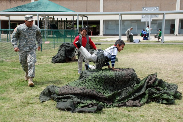 Spc. Sammy Rosado of the 470th Military Intelligence Brigade supervises two Bowden Elementary School students as they master an obstacle course during their field day April 5. The brigade conducted the field day in partnership with the school as part of the Joint Base San Antonio Adopt-a-School Program. (U.S. Army photo by Gregory Ripps)
