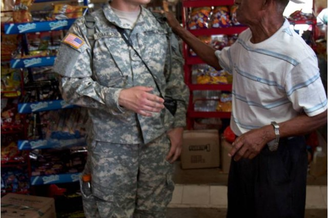 """ESCOBAL, Panama (April 4, 2013) """" Pfc. Adam Wakeland, a nuclear biological specialist and unit photographer with 961st Engineer Battalion, a Reserve unit out of Seagoville, Texas, talks to a Panamanian man at a market during operations for U.S. Army South's Beyond the Horizon-Panama."""