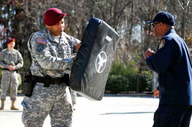 Sgt. Shawn Dean, a military police officer for the 21st Military Police Company, 503rd Military Police Battalion (Airborne), braces for impact as Earl Britt, a civilian law enforcement sergeant for the Department of the Army, demonstrates the proper use of the armament and service protocol baton, March 21. This training is part of a two-week annual certification course. (Photo by Sgt. Christopher Freeman/50th PAD)