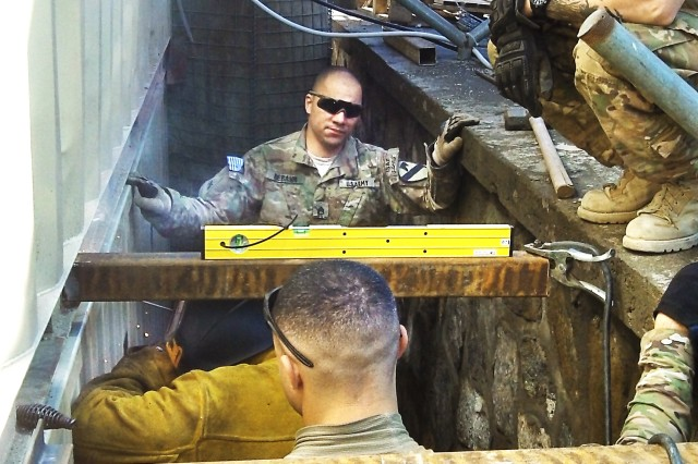 From front: Sgt. Jason Aguilar, Sgt. Marco Palomo, Staff Sgt. Joshua Debaun and (kneeling above) RFAST-C mechanical engineer Nick Merrill assemble and weld the floor framework at the Security Forces Advise and Assist Team-8 compound.