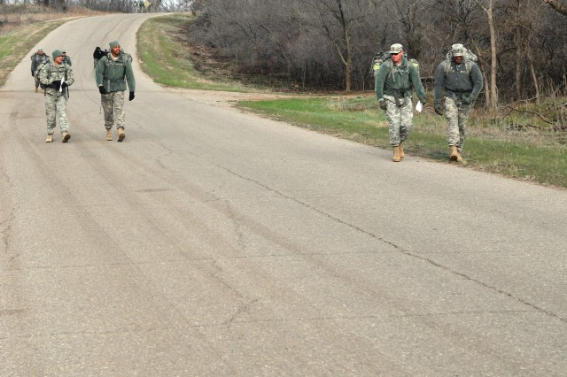 "Three of the 60 two-Soldier teams in the ""Poker Ruck"" challenge move down a road en route to their first point March 27. While carrying 35- to 45-pound rucksacks, Soldiers navigated to 10 points from each they received a playing card to form their best five-card poker hand."