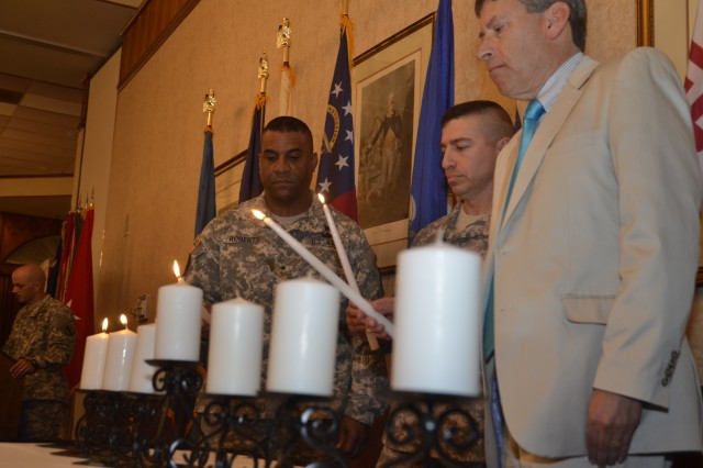 From left, Brig. Gen. Bryan Roberts, Fort Jackson commanding general, Command Sgt. Major Michael McCoy, commandant of the Drill Sergeant School, and Dr. Henry B. Miller, guest speaker, light seven candles in honor of the victims of the Holocaust.