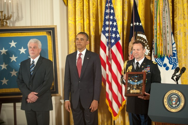 President Barack Obama and Ray Kapaun (left), nephew of Chaplain (Capt.) Emil J. Kapaun, who was posthumously awarded the Medal of Honor during a ceremony in the East Room of the White House, Washington, D.C., April 11, 2013, stand during the reading of the award citation.