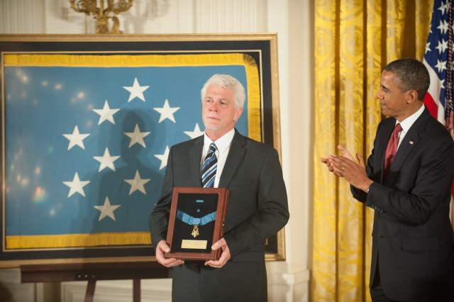 Ray Kapaun (left), nephew of Chaplain (Capt.) Emil J. Kapaun, accepted the Medal of Honor for his uncle, who was posthumously awarded the Medal of Honor during a ceremony in the East Room of the White House, Washington, D.C., April 11, 2013, as President Barack Obama leads the audience in a round of applause.