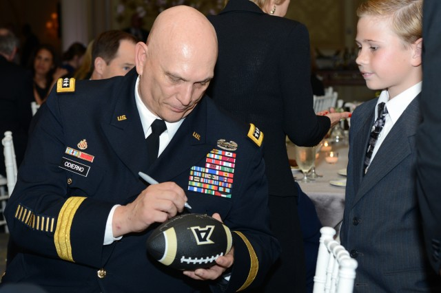 Army Chief of Staff Gen. Ray Odierno signs a football for Nate Richards, who was last year's recipient for the Military Child of the Year award for the Navy.