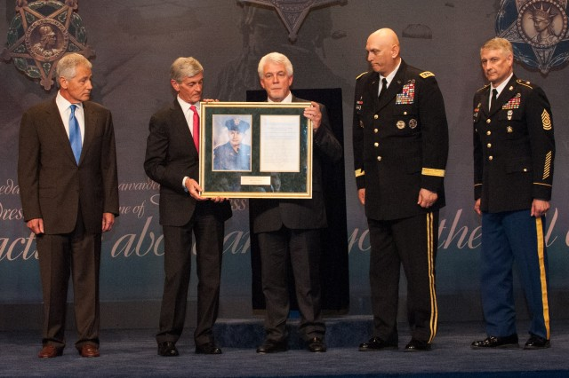 Secretary of the Army The Honorable John McHugh presents Medal of Honor recipient Chaplain (CPT) Emil J. Kapaun's nephew Mr. Ray Kapaun with a photo and citation as Secretary of Defense Chuck Hagel (far left), U.S. Army Chief of Staff Gen. Raymond T. Odierno (right), and Sergeant Major of the Army SMA Raymond F. Chandler (far right) watch during the Hall of Heroes Induction Ceremony of Chaplain (CPT) Kapaun at the Pentagon April 12, 2013. Chaplain (CPT) Kapaun was posthumously  awarded the Medal of Honor on April 11, 2013.  (U.S. Army photo by Staff Sgt. Steve Cortez/ Released))