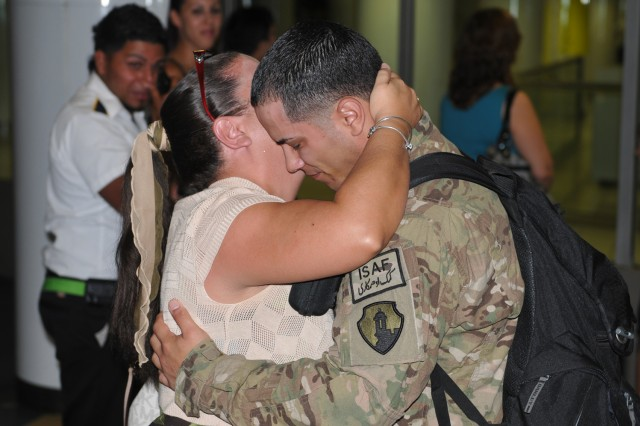 A soldier assigned to the 393rd Combat Sustainment Support Battalion is received by a family member, 12 April at the Luis Muñoz Marin International Airport, Carolina, Puerto Rico.