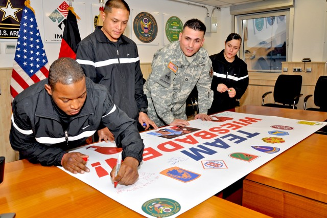 Pfc. Nathaniel Barnd signs the Wiesbaden boxing team banner with fellow boxers and Coach Adam Martinez in preparation for a tournament in Grafenwoehr.