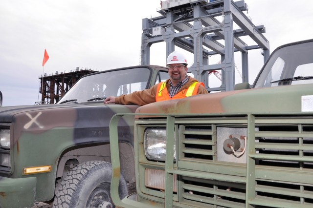 With a dam shell lifting frame and the super gantry crane in the background, Hawley stands between two of the 10 5/4-ton Chevy pickups he has acquired through GSAXcess and saved the Olmsted Locks and Dam construction project tens of thousands of dollars.