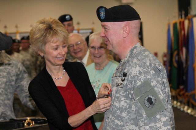 Helen Bosse removes her husband's colonel rank and replaces it with the insignia of brigadier general during his promotion ceremony at the 87th United States Army Reserve Support Command (East) April 14.