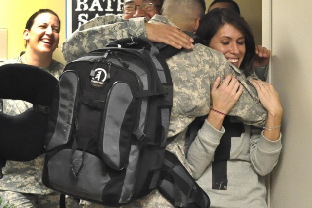 Sgt. Joshua Holt, 12th Public Affairs Detachment, greets his wife and comrades Jan. 28, 2013 during a welcome home gathering after returning from a nine-month deployment to Camp Arifjan, Kuwait. Holt, a native of Bristol, Tenn., documented key leader engagements as a photojournalist. The 12th PAD visited more than eight countries in support of the Third Army/ARCENT communication, whose area of operations includes 20 countries in the Middle East and Central Asia.