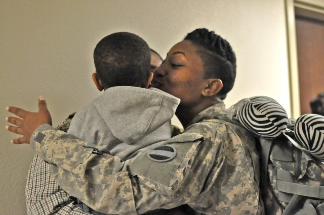 Sgt. 1st Class Paige Fluker, 12th Public Affairs Detachment, greets her son and husband Jan. 28, 2013 during a welcome home gathering after returning from a nine-month deployment to Camp Arifjan, Kuwait. Fluker's duty assignments included senior noncommissioned officer of the 12th PAD while they supported more than eight countries in support of the Third Army/ARCENT.