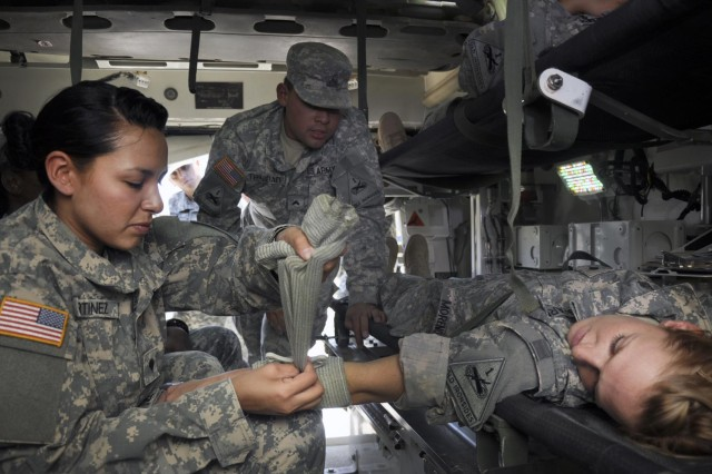 Cpl. Dariel Trinidad, medic with the 1st Brigade Combat Team, 1st Armored Division, trains Spc. Kathy Martinez to apply pressure bandages during pre-deployment Tactical Combat Casualty Care for the Female Engagement Team, at Fort Bliss, Texas.