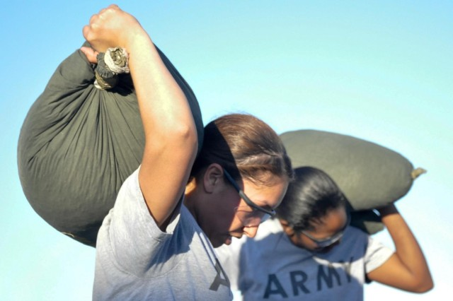 Pfc. Ana G. Walker and Spc. Janae Gaston lift sandbags during physical training for the Female Engagement Team, on East Fort Bliss, Texas.