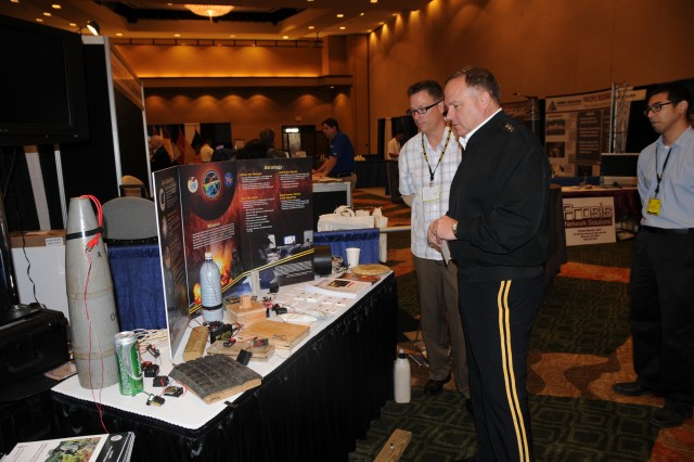 "Glenn Cober from the Asia-Pacific Counter-Improvised Explosive Device Center speaks with U.S. Army Pacific, Commanding General, Lt. Gen. Francis J. Wiercinski at AP-CIED display, April 11 at the LANPAC Symposium and Exposition held from April 9 "" 11at the Sheraton Waikiki Hotel in Honolulu."