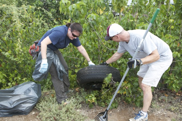 Stefanie Gardin, public affairs officer for U.S. Army-Garrison Hawaii, and Sgt. 1st Class John Freese, operations noncommissioned officer for the 9th Mission Support Command work together to pull an old tire from the bushes during the Pearl Harbor Bike Path Clean-Up, here, April 6.